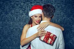 Hombre de abarcamiento de la mujer joven de santa con la caja de regalo en la Navidad Fotografía de archivo