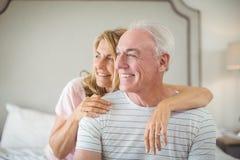 Hombre de abarcamiento sonriente de la mujer en cama Imágenes de archivo libres de regalías