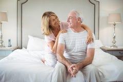 Hombre de abarcamiento sonriente de la mujer en cama Fotos de archivo libres de regalías