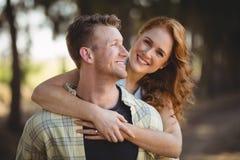Hombre de abarcamiento sonriente de la mujer en la granja verde oliva Foto de archivo