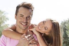 Hombre de abarcamiento sonriente de la mujer joven de detrás en parque Imagen de archivo libre de regalías