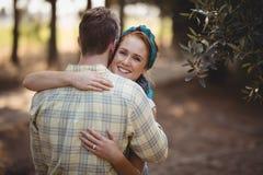 Hombre de abarcamiento sonriente de la mujer joven en la granja verde oliva Imagen de archivo libre de regalías