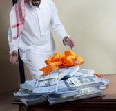 Hombre de Arabia Saudita sorprendido con las pilas de dinero en la tabla imágenes de archivo libres de regalías