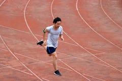 Hombre de Asian del atleta que corre en pista en estadio Concepto activo sano de la forma de vida Foto de archivo