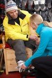 Hombre de ayuda auxiliar de las ventas para intentar encendido las botas de esquiar Fotos de archivo libres de regalías