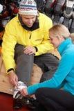Hombre de ayuda auxiliar de las ventas para intentar encendido las botas de esquiar Foto de archivo