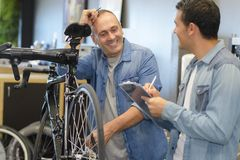 Hombre de ayuda del vendedor para comprar la bici derecha Fotografía de archivo libre de regalías