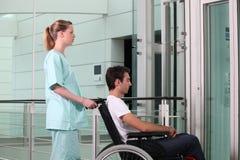 Hombre de ayuda en silla de ruedas foto de archivo libre de regalías