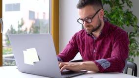Hombre de Beared en los vidrios que sientan en casa la oficina y que trabajan en un ordenador portátil