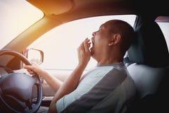 Hombre de bostezo soñoliento que conduce el coche en tráfico después de la impulsión de la largas horas Foto de archivo