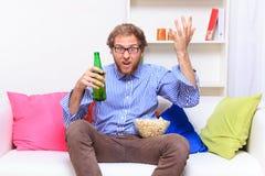 Hombre de Dissatisfacted en el sofá al ver la TV Fotos de archivo libres de regalías