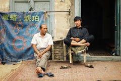 hombre de dos uyghur delante de su joyería imagen de archivo