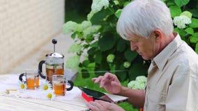 Hombre de Eldary que usa la tableta digital en tabla del jardín del verano con té almacen de metraje de vídeo