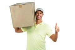 Hombre de entrega alegre con la caja que muestra los pulgares para arriba Fotografía de archivo