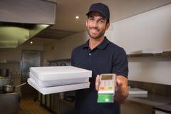 Hombre de entrega alegre de la pizza que sostiene la máquina de la tarjeta de crédito Fotografía de archivo