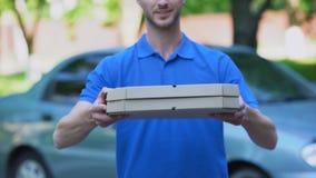 Hombre de entrega amistoso que da la caja de la pizza, orden de la comida en línea, servicio del restaurante almacen de metraje de vídeo