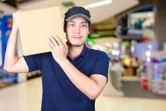 Hombre de entrega asiático de la sonrisa con la caja de cartón a disposición que se coloca adentro Imagen de archivo