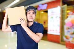 Hombre de entrega asiático de la sonrisa con la caja de cartón a disposición que se coloca adentro Fotografía de archivo