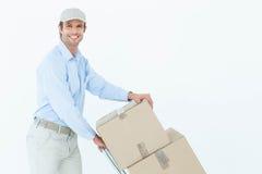 Hombre de entrega confiado que empuja la carretilla de las cajas de cartón Fotos de archivo libres de regalías