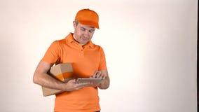 Hombre de entrega en uniforme de la naranja usando su tableta y el donante de un paquete al cliente Tiro aislado 4K gris del back metrajes