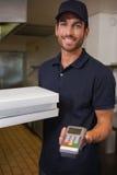 Hombre de entrega feliz de la pizza que muestra la máquina de la tarjeta de crédito Imagen de archivo