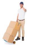 Hombre de entrega feliz que empuja la carretilla de cajas Imágenes de archivo libres de regalías