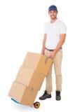 Hombre de entrega feliz que empuja la carretilla de cajas Fotografía de archivo libre de regalías