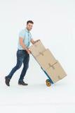 Hombre de entrega feliz que empuja la carretilla de cajas Imagen de archivo