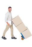 Hombre de entrega feliz que empuja la carretilla de cajas Fotos de archivo libres de regalías
