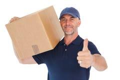 Hombre de entrega feliz que sostiene la caja de cartón que muestra los pulgares para arriba Imagenes de archivo