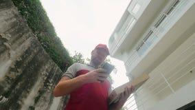 Hombre de entrega de la pizza que usa la dirección del hallazgo del smartphone de la casa moderna almacen de metraje de vídeo