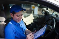 Hombre de entrega que comprueba orden y la dirección del cliente en su camión imagenes de archivo