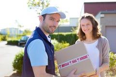 Hombre de entrega que entrega un paquete al cliente Fotos de archivo