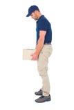 Hombre de entrega que lleva el paquete pesado en el fondo blanco Imagen de archivo