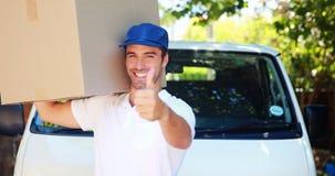 Hombre de entrega que lleva un paquete almacen de video
