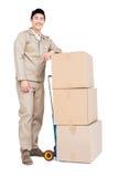 Hombre de entrega que se coloca al lado de la carretilla del equipaje con las cajas de cartón Imagen de archivo