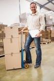 Hombre de entrega que se inclina en la carretilla de cajas Fotografía de archivo libre de regalías