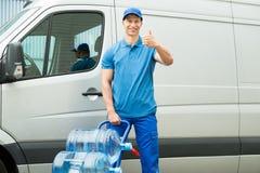 Hombre de entrega que sostiene la carretilla con las botellas de agua imágenes de archivo libres de regalías