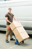 Hombre de entrega que sostiene la carretilla con las cajas de cartón Foto de archivo libre de regalías