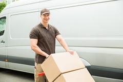 Hombre de entrega que sostiene la carretilla con las cajas de cartón Fotos de archivo