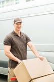Hombre de entrega que sostiene la carretilla con las cajas de cartón Imagenes de archivo