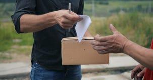 Hombre de entrega sonriente en la camisa gris oscuro estricta que entrega la caja del paquete al beneficiario - concepto del serv almacen de video
