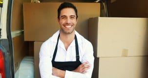 Hombre de entrega sonriente que se sienta en su furgoneta almacen de metraje de vídeo