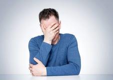Hombre de Facepalm, varón del retrato en la camiseta que se sienta en una tabla, emoción épica del fall fotografía de archivo libre de regalías