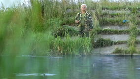 Hombre de Fisher con los pescados de cogida de la caña de pescar en el lago almacen de video