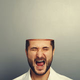 Hombre de griterío con la cabeza abierta sobre gris Imagen de archivo