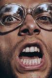 Hombre de griterío enojado en vidrios Imagen de archivo