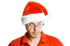 Hombre de inclinación sin afeitar de los ojos en el sombrero de Papá Noel Aislado en blanco Humo Foto de archivo libre de regalías