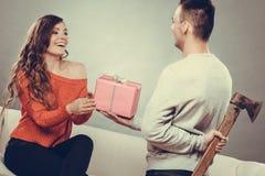 Hombre de Insincire que sostiene el hacha que da la caja de regalo a la mujer Imagenes de archivo