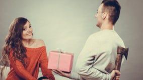 Hombre de Insincire que sostiene el hacha que da la caja de regalo a la mujer Fotos de archivo libres de regalías
